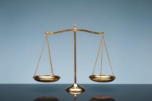 Golden brass balance or imbalance scale on blue color background. Weight balance. Symbol of law justice, libra, decision, crime, financial.