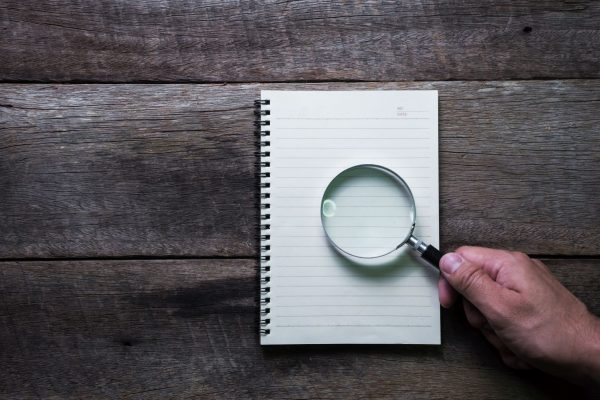 note book and Magnifier on wood table